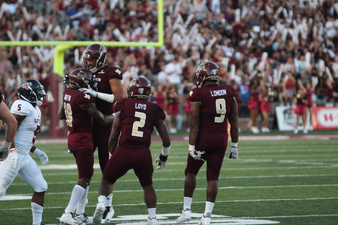 Texas State defense players number 18, 2, and 9 celebrate after a big play.