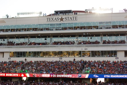 The sun sets behind the stands and press boxes of Bobcat Stadium.