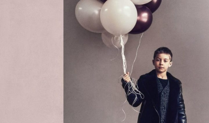 Boy holding white, gray and purple balloons