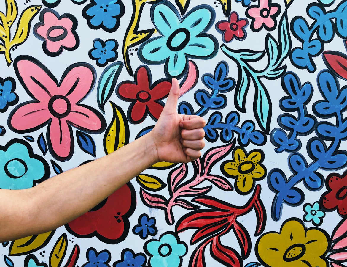 An arm with a thumbs up in front of a brightly colored floral mural.