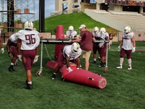 On a cloudy day in San Marcos, the defensive line, in white jerseys, practices scurrying under a netting to pop a practice dummy bag. Number 73 Jaquel Pierce is pictured finishing the tackling.