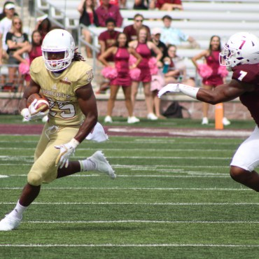 In a golden jersey, number 25, running back Anthony D. Taylor breaks away from the clutches of number seven on the ULM defense. Brown's dreadlocks quickly whip to the right, showing the agility he made the cut with as his eyes are focused on dead-center field.