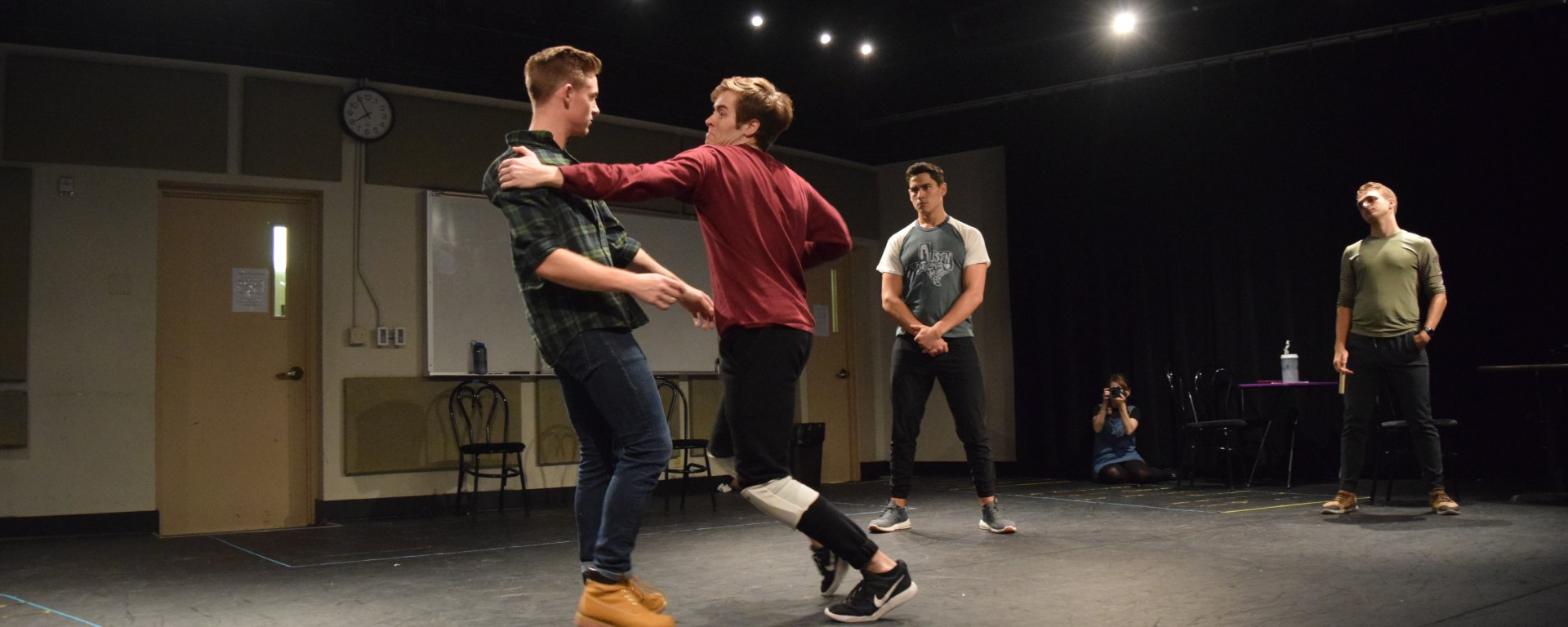 In the rehearsal room, the cast of Cabaret rehearses fight choreography.