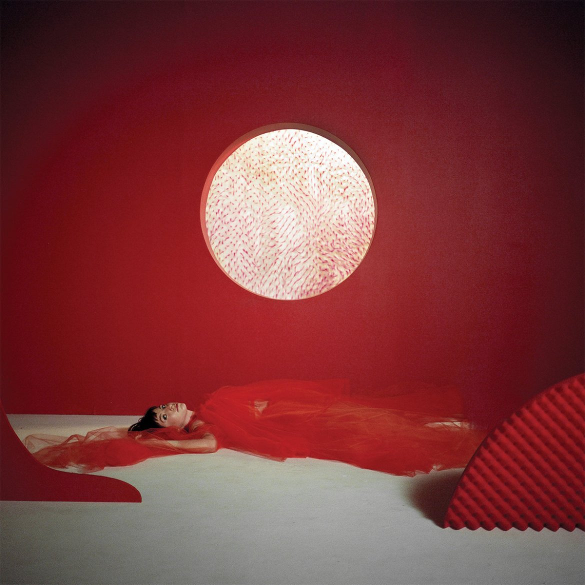 A woman in red tulle lying on the ground with a red backdrop and white circle.