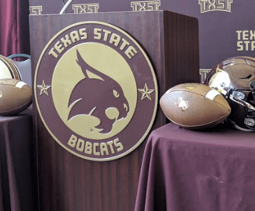 A podium, two footballs, and two helmets with the Bobcat logo.