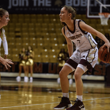 A Texas State player faces off against a Nicholls State player.