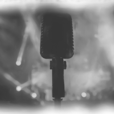 A microphone is in the foreground of the photo, only the head is visible. Behind it, there is a stage with spotlights on it.