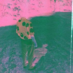 The album cover is a headless figure wearing striped slacks and a polka-dot shirt standing in a pink scene and on a dark purple ground with his pink shadow.