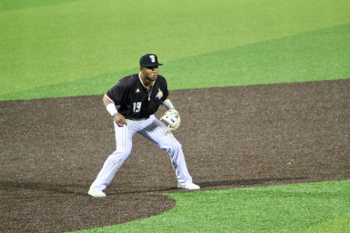 A baseball player on the field waiting for the ball to come his direction.
