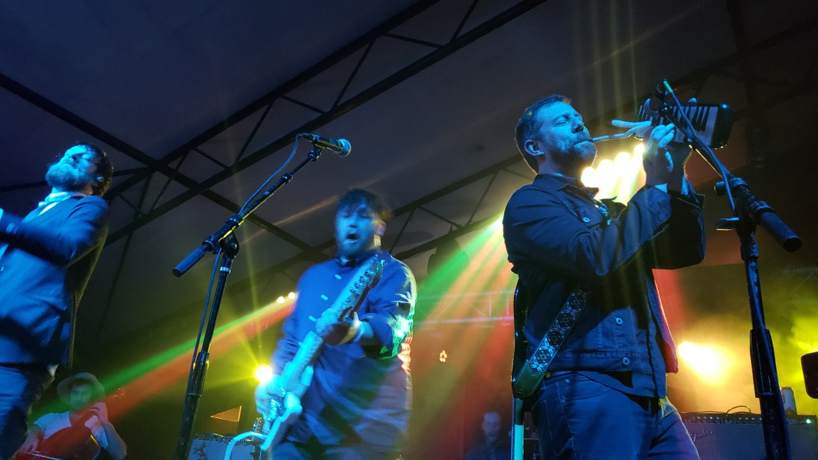 Three men on stage performing at their album release concert.