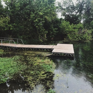 There is a wooden dock jutting out onto the river and there is lots of greenery surrounding the dock.