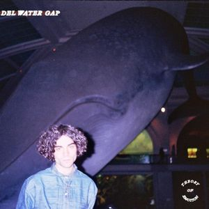 A dark photograph of Holden Jaffe, singer from Del Water Gap, in front of a whale in a museum.