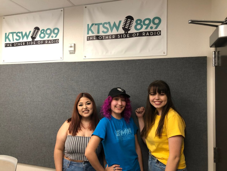 Three girls pose on front of KTSW banner.