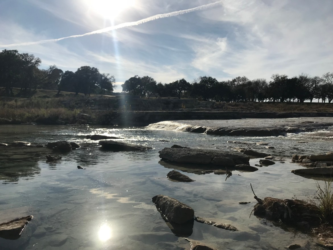 picture of the Blanco River with rocks and sun in the background
