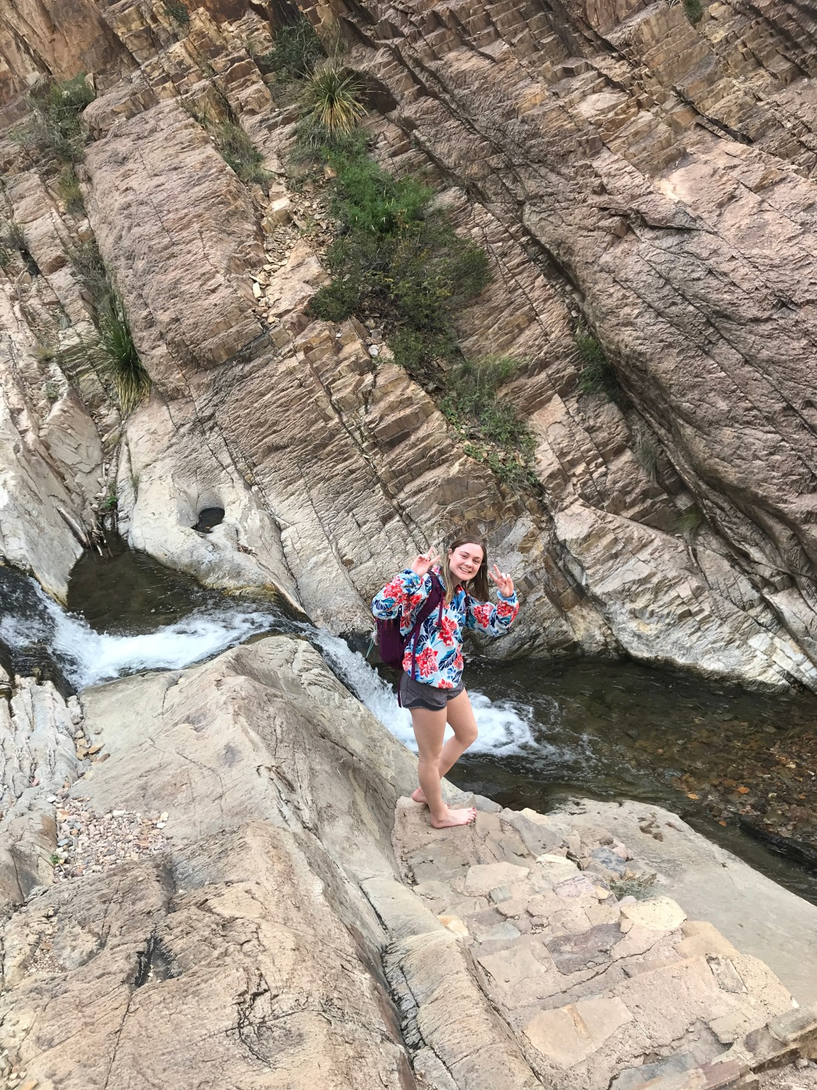 White girl wearing sweaters and shorts with no shoes posing in front of a river flowing over a trail