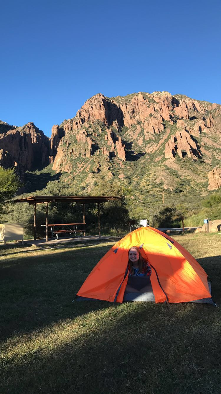 girl sticking her head out of an orange tent with mountains in the background