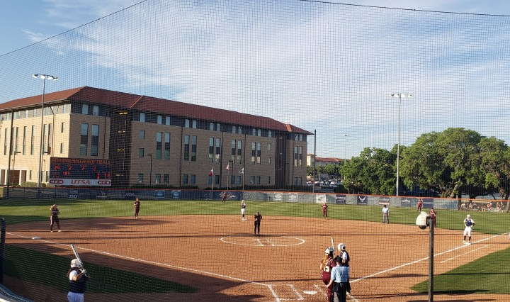 Texas State Softball on defense against UTSA with several Texas State players on the field in position.