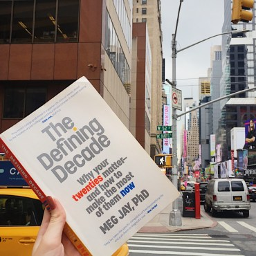 """A copy of """"The Defining Decade"""" by Dr. Meg Jay held up from a New York street against Times Square buildings."""