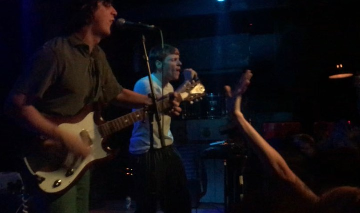 Two guys on stage, one with curly dark hair playing guitar and singing, the other with straight light hair singing and playing the synth.