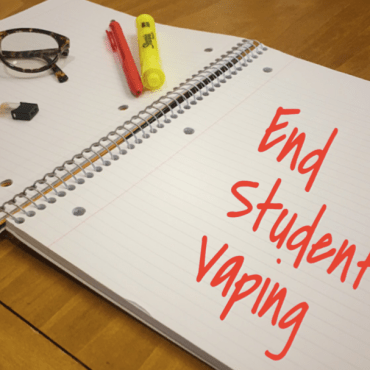 Glasses, pens, and JUUL pods rest on a notebook representing a 2019 student's school supplies.