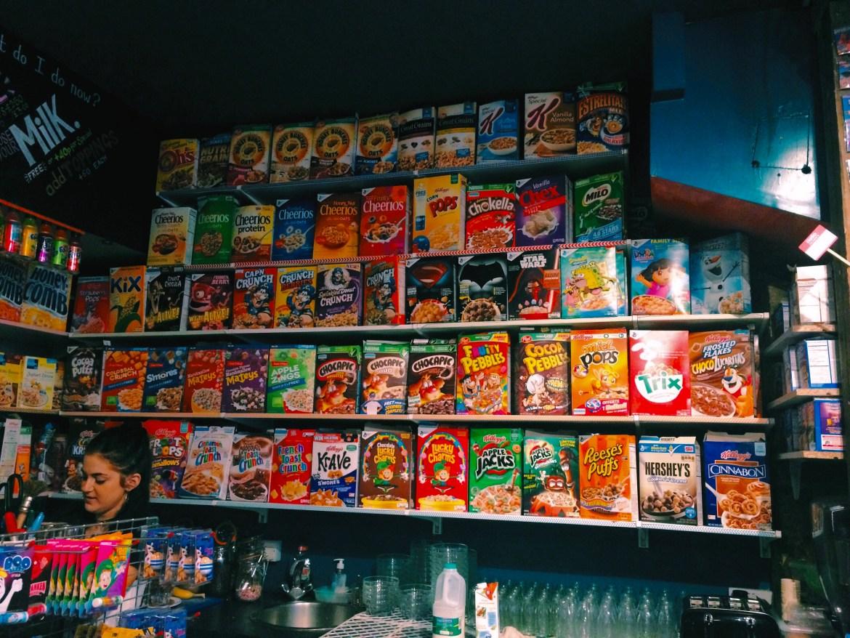"A colorful shelf of cereal boxes inside London's ""Cereal Killer Cafe."""