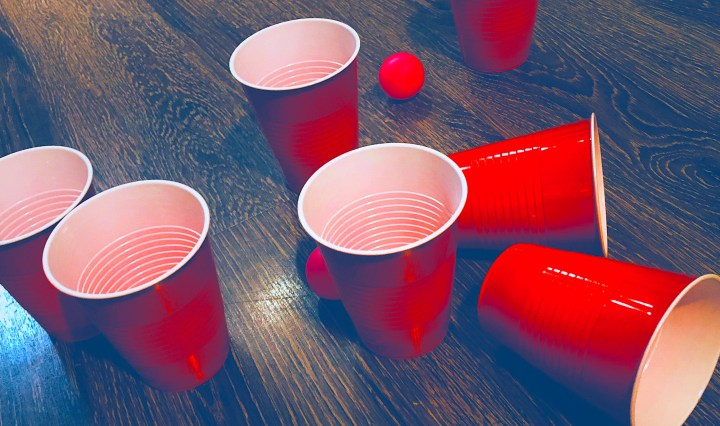 Collection of red solo-cups on the ground. A few ping-pong balls are set around them.