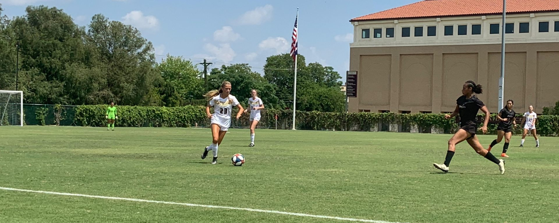 Blonde Texas State player kicks the soccer ball at midfield