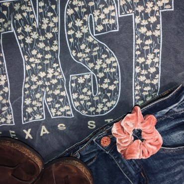 Gray shirt with TXST spelt on it with blue jean shorts and a pink scrunchie on top. With Birkenstocks to go with it.