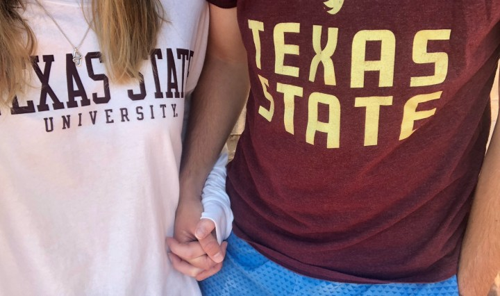 A boy and girl holding hands. Girl is in white shirt. Boy is in maroon shirt.