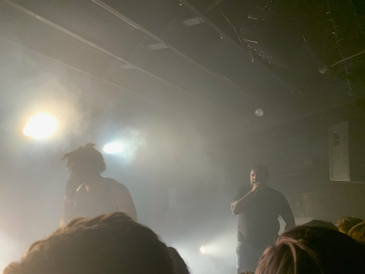 The picture features two members from Injury Reserve - (Stepa J. Groggs and Ritchie With a T) rapping at their concert in Austin.
