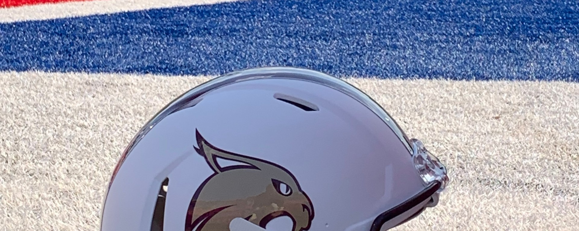 A white football helmet on the field with red, white, and blue painted turf