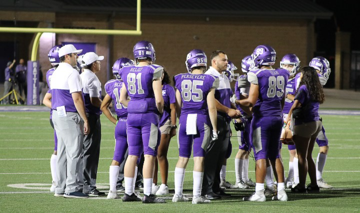 Young men in Purple uniforms and helmets listen to their coaches.