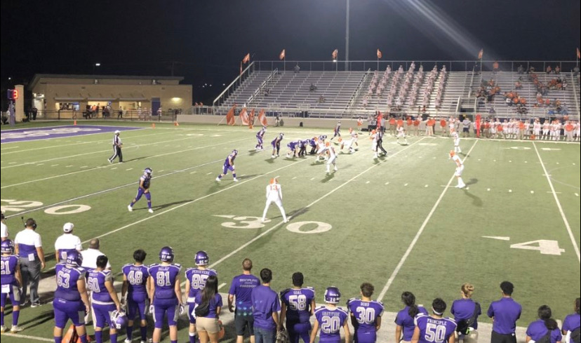 San Marcos is wearing their purple uniforms as they drive the ball downfield against Laredo who is in the white uniforms with orange helmets.