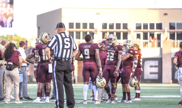 """Senior linebacker Bryan London wearing a maroon jersey with his helmet off talks with his teammates on the field during a break in the Bobcats """"Battle for the Paddle"""" matchup against the Nicholls Colonels."""