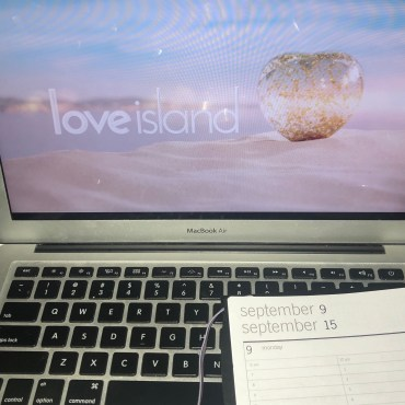 The Love Island title screen on a laptop screen and a daily planner on the lower left hand corner.