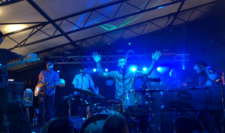The picture shows six band members tuning their instruments with a blue light shining above them. The drummer, who is in the center of the stage, has his hands raised.
