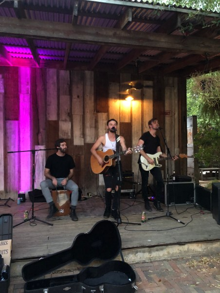 three members of the band, 2 standing and 1 sitting, performing on an outdoor patio with a cover, in the late evening