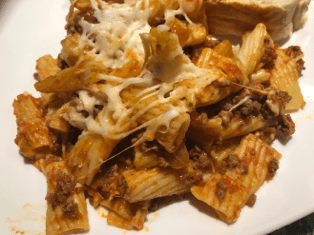 Rigatoni pasta with meat sauce on a white plate. Cheese is stringing from the noodles.