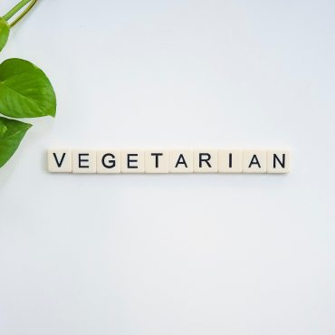 """Small tiles spelling out the word """"vegetarian"""" with a leafy green plant in the corner."""