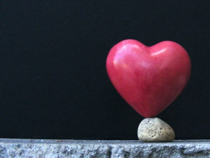 A red heart balancing on a small rock in front of a black background