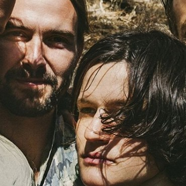 The members of Big Thief huddled in close for a photo.