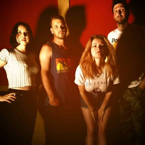 Shot of the four members of Black Basements, with deep shadows, standing in front of a dark red wall.