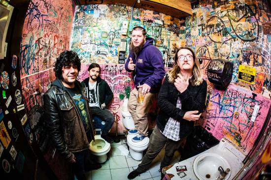 The members of Gold Leather are posing in an empty bathroom with heavily graffitied walls.