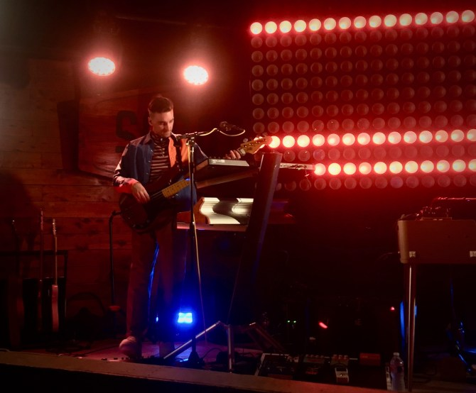 A man playing bass on a stage with red lights shining on him