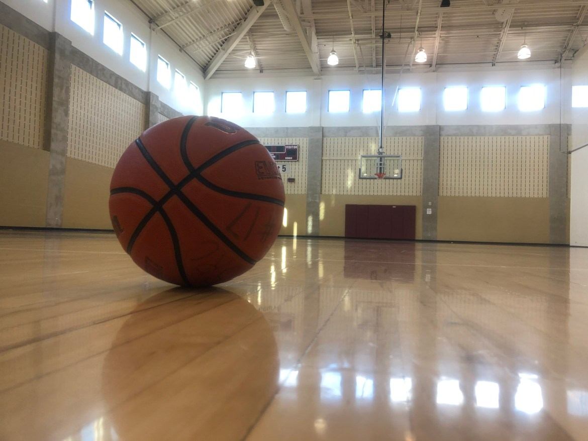 A basketball sitting on a court with the net in the background.
