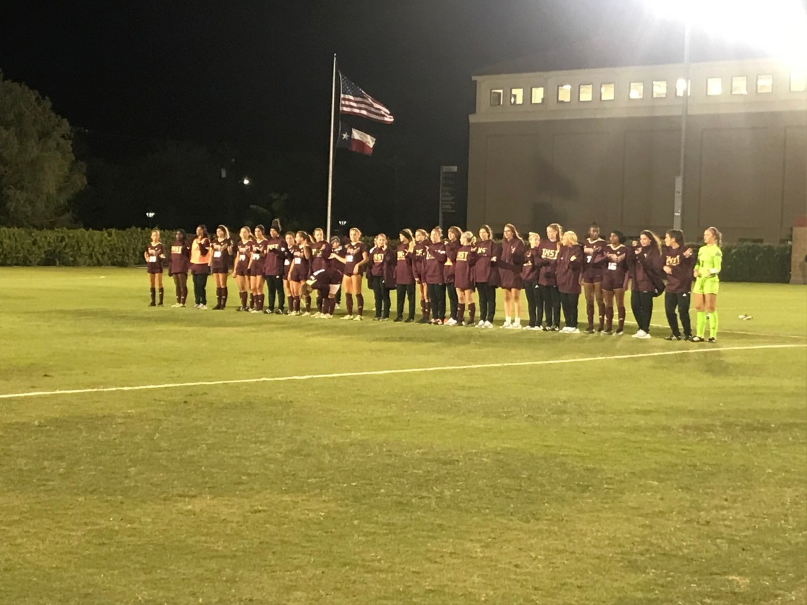 The Bobcats line towards the center of the field facing the crowd to sing the Alma Mater. The American Flag and Texas Flag are waving in the background on a cold, windy night.