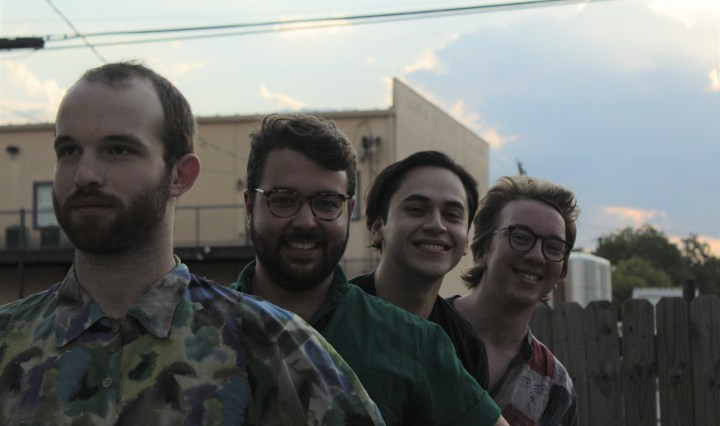 four people stand in a line in front of an apartment building with a cloudy sky above them. Three of the people are smiling while the one in front looks off in the distance with a serious look.