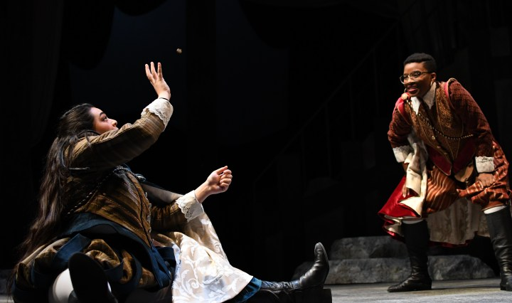 Two women in period costumes catching a coin in the air.