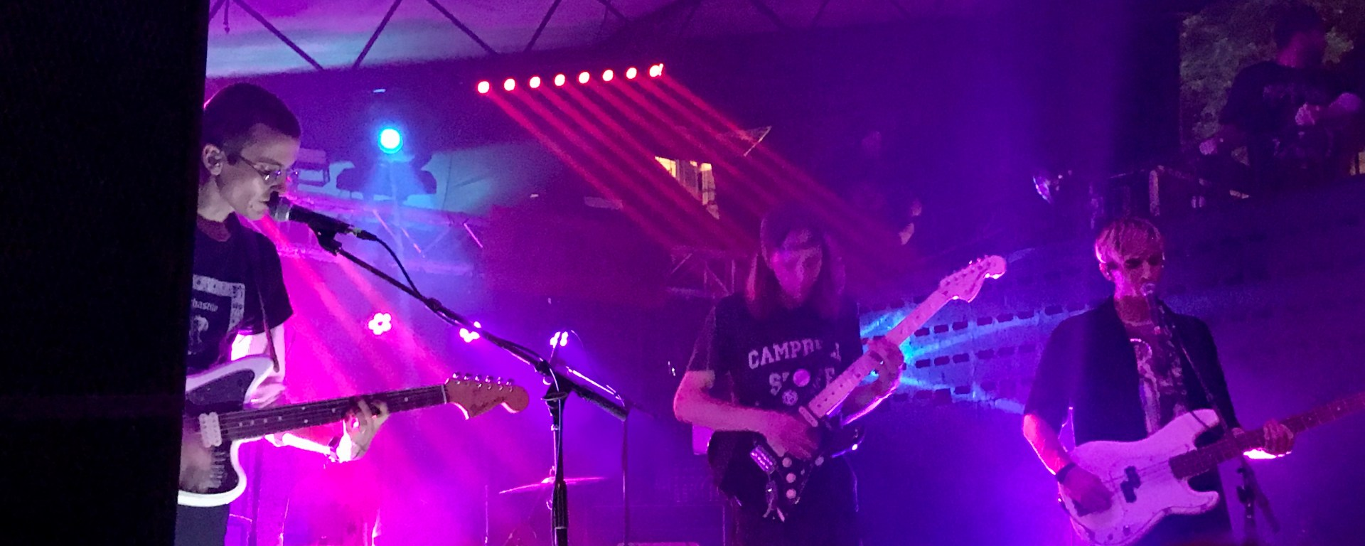Members from the band DIIV performing live on stage amidst multiple lights.