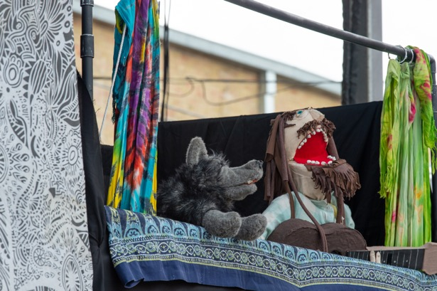 Two puppets peek out from a makeshift stage made of bandanas and blankets draped over PVC pipes. The puppets are a wolf on the left and a man with a brown beard on the right.